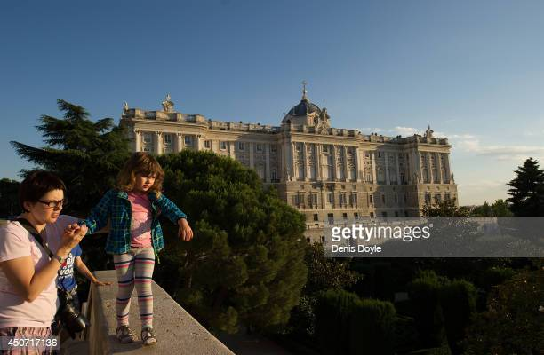 A mother holds her daughter as she walks on a high wall over the Sabatini gardens with the Royal palace in the background on June 16 2014 in Madrid...
