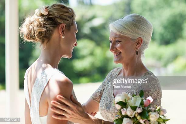 Mère embrassant la mariée le jour du mariage