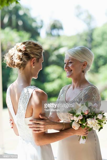 Mother hugging bride on wedding day