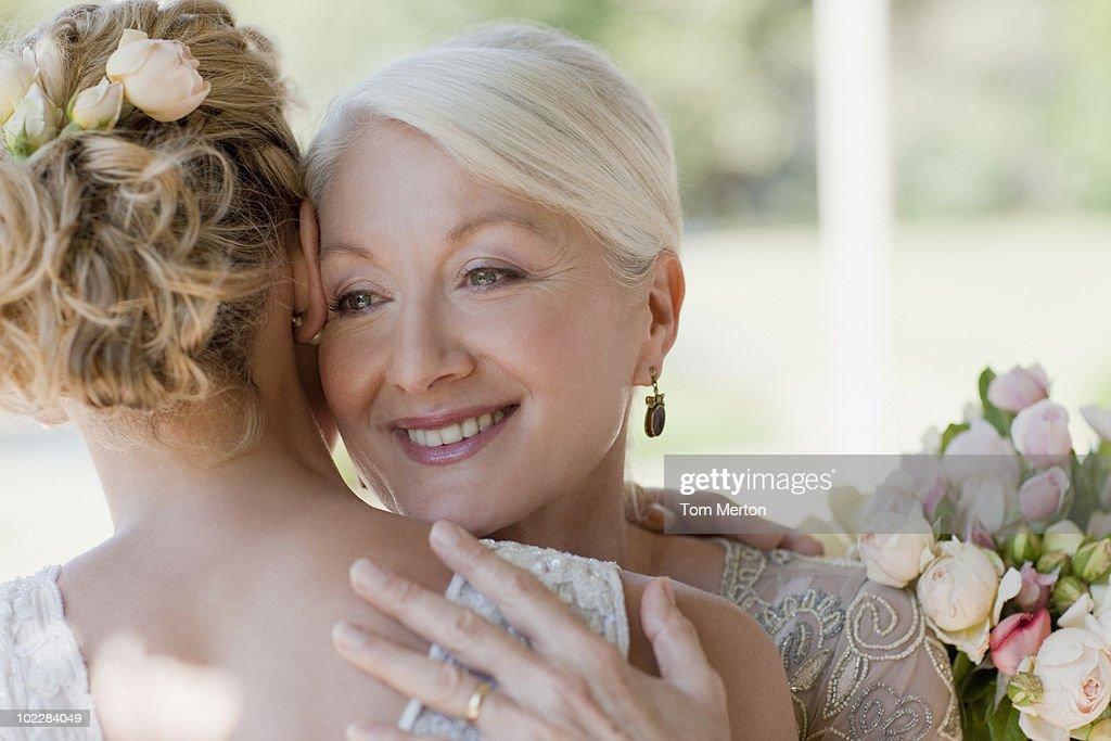 Mother hugging bride : Stock Photo