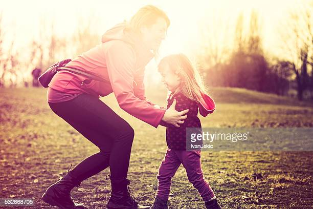 Mother hugging child in park at sunset