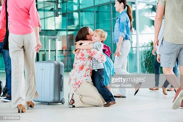 Mother hugging children at airport