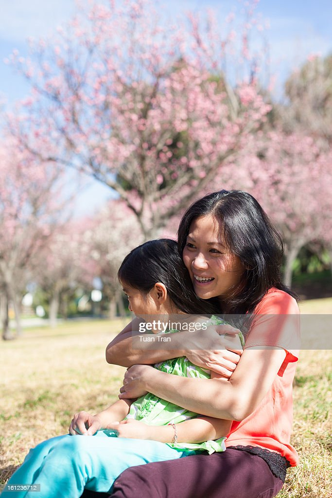 mother hugging daughter at the park : Stock Photo