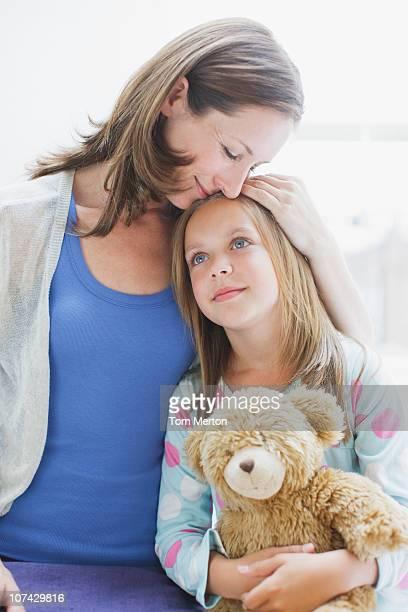 Mother hugging daughter holding teddy bear