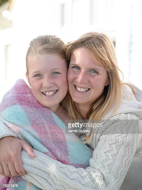 Mother hugging daughter (8-10) in blanket