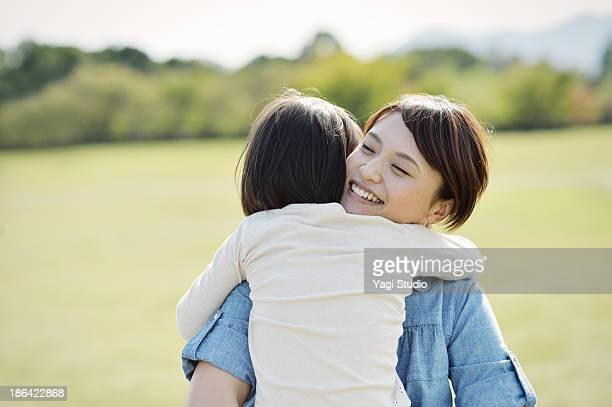 Mother hugging daughter in greeng
