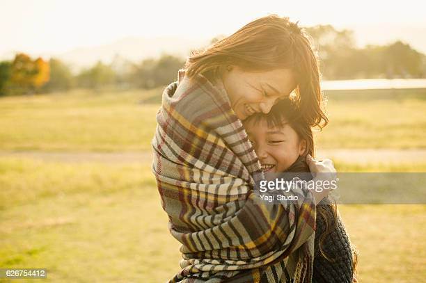 Mother hugging daughter in outdoors