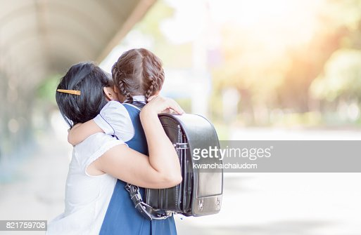 mother hugging daughter in uniform student : Stock Photo