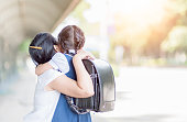 mother hugging daughter in uniform student, love concept