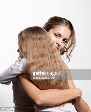Mother hugging daughter : Stock Photo