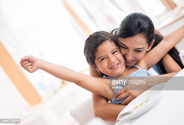 Mother hugging her daughter after she ate dinner