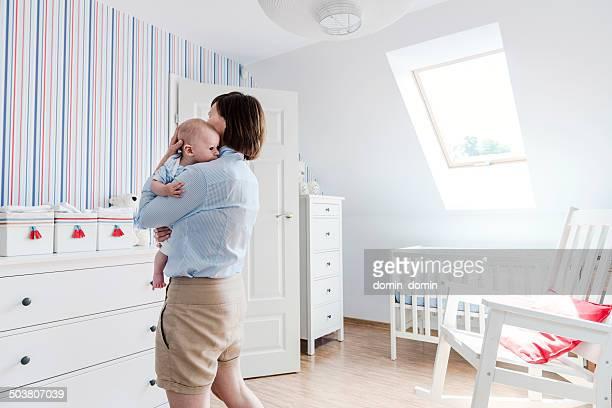 Mother hugging little baby boy tenderly, home interior