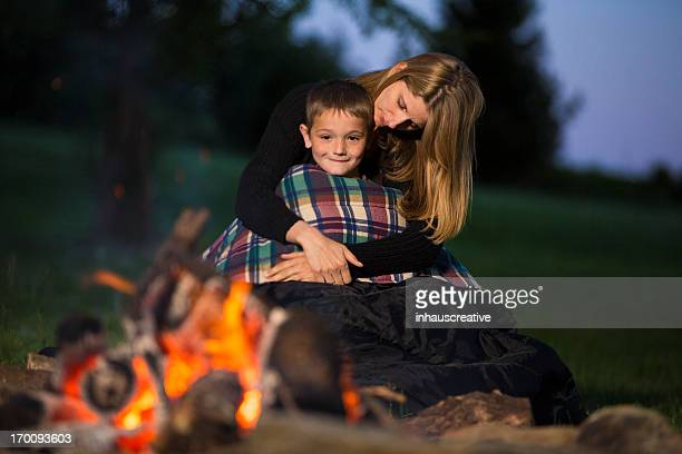 Mother hugging son at campfire