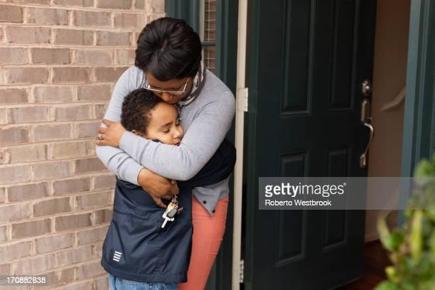 Mother hugging son at front door