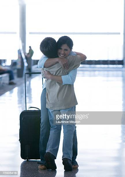 Mother hugging son in airport