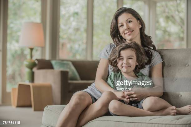 Mother hugging son on sofa