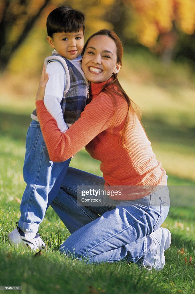 Mother hugging son outdoors : Stock Photo