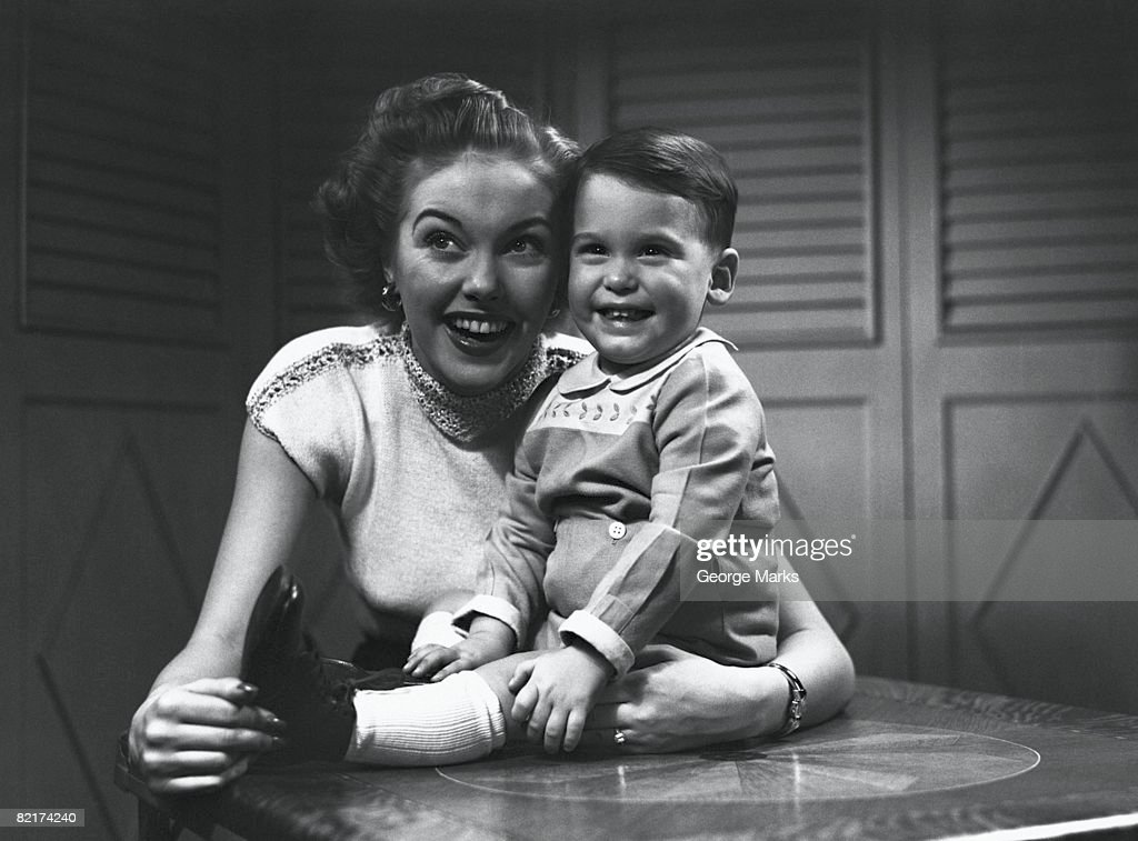 Mother hugging son (2-3) sitting on table, (B&W) : Stock Photo