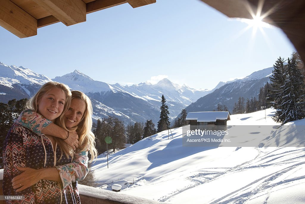 Mother hugs daughter at mountain chalet, sunrise : Stock Photo