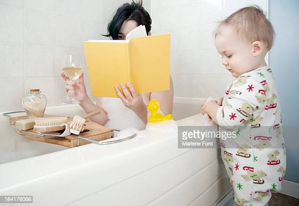 Mother in bathtub with toddler beside tub