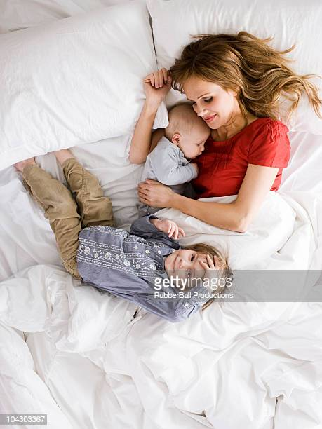 mother in bed with two young children