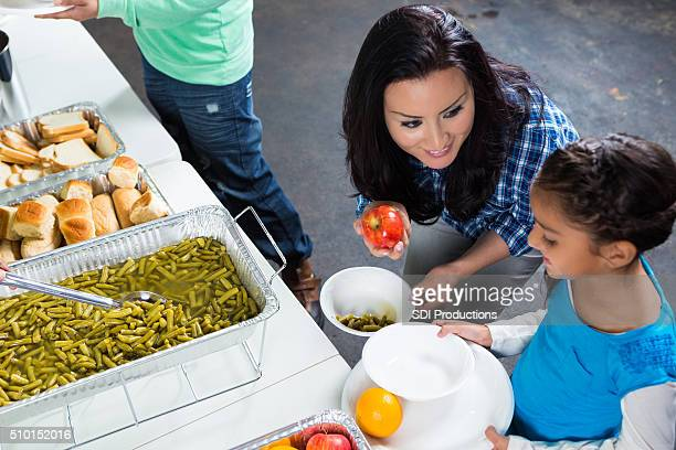 Mother in daughter in line at soup kitchen