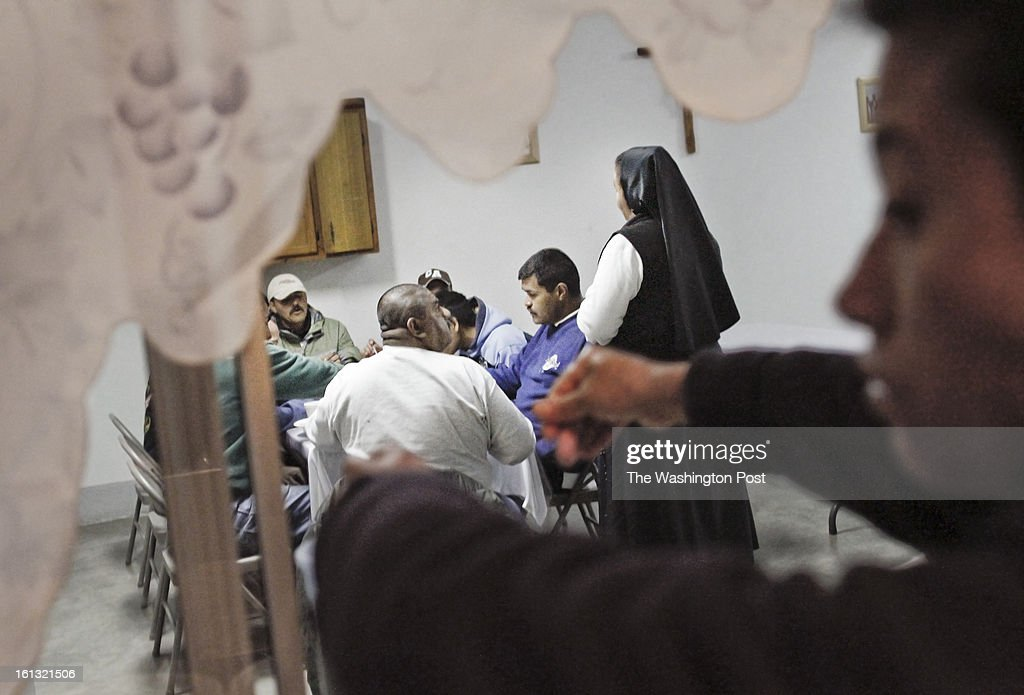 Mother Ines (at right in background), the Catholic nun who manages the 'Casa Migrante', an immigrant shelter in Tecate, Baja California, Mexico, talks to a group of immigrants during dinner at her facility on February 7, 2013. This immigrant shelter houses and feeds thousands of immigrants every year. With a total capacity of 40 beds, male migrants can stay in the premises for a total of 4 nights before moving on. Places such as Casa Migrante are popular amongst immigrants and deportees making their way back into the United States. (Javier Manzano / For The Washington Post via Getty Images).