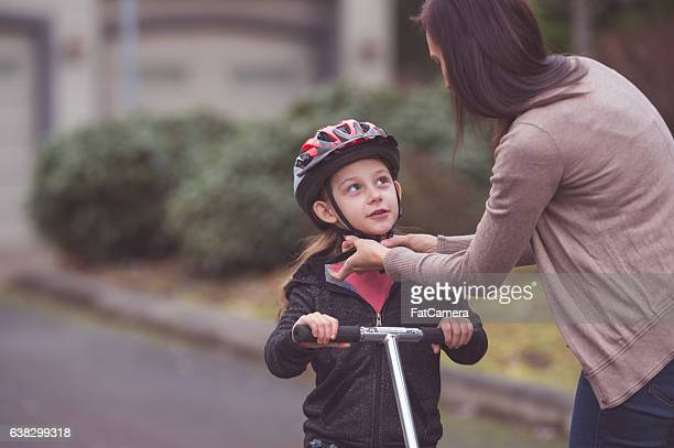 A mother is helping her daughter put on a bicycle