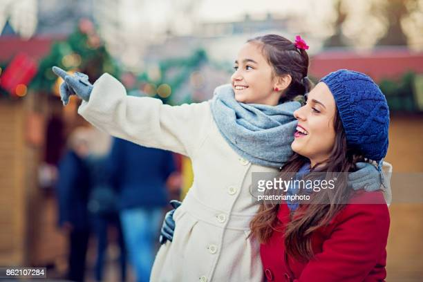 Mother is hugging her beloved daughter at the Christmas market