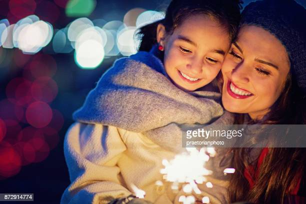 Mother is hugging her daughter at Christmas