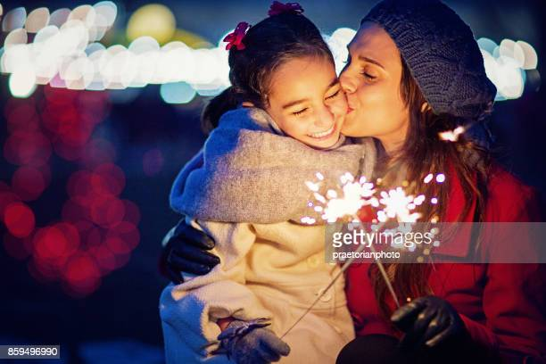 Mother is kissing her daughter at Christmas
