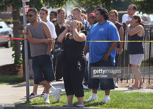 A mother is overcome with grief as she watches while police investigate the scene of her son's murder July 28 2008 in Chicago Illinois Her son was...