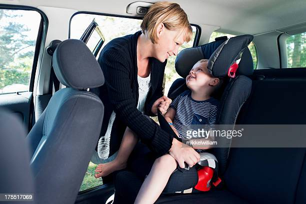 Mother is securing child in a car with seat belt