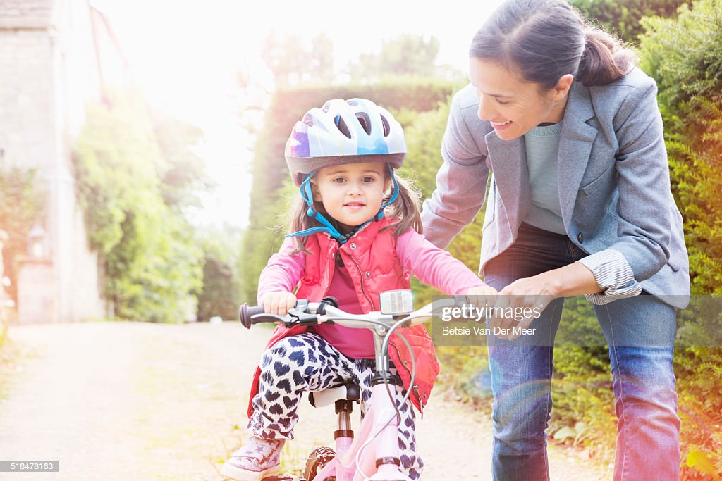 mother is teaching her daughter cycling.