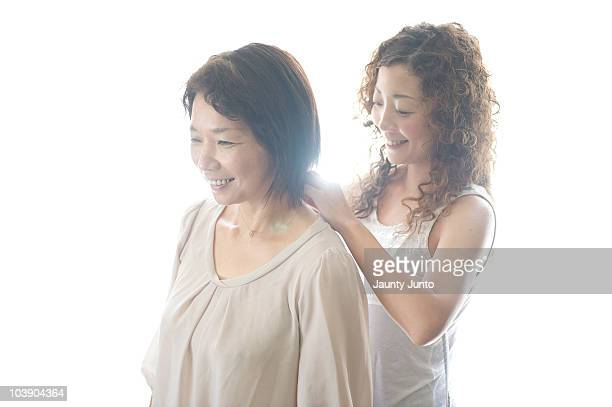 mother is worn the neckless by her daughter