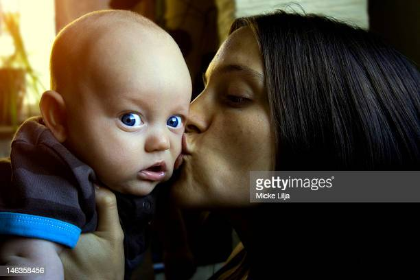 Mother kisses baby boy on cheek