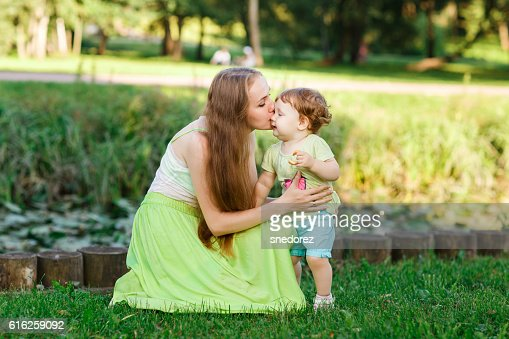 Mother kisses daughter in park on green lawn : Stock Photo