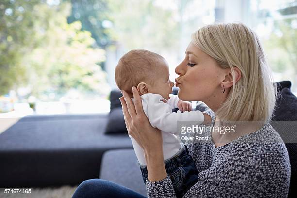 Mother kissing baby at home