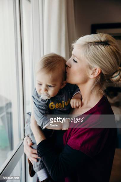 Mother kissing baby boy on head in front of window