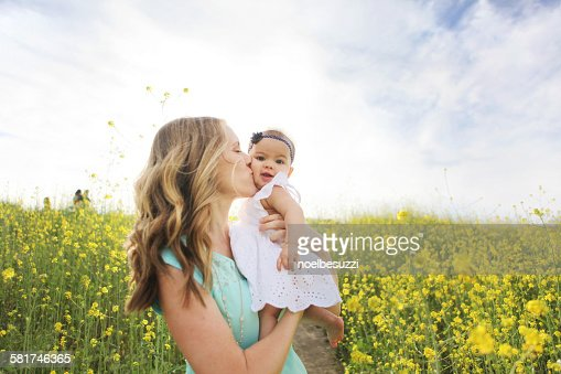Mother kissing baby girl in field of flowers