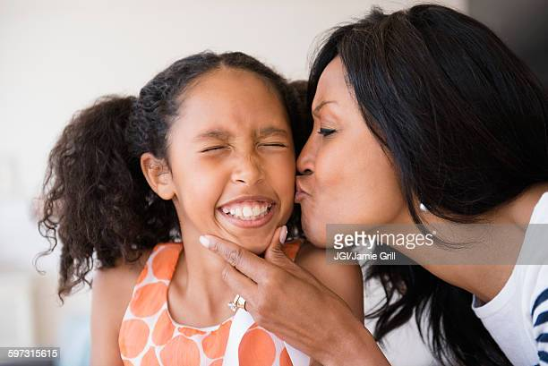 Mother kissing cheek of squinting daughter