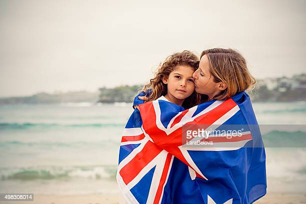 Mother kissing daughter and they are covered by Australian flag