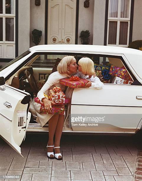 Mother kissing daughter in car