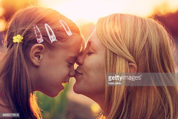 Mother kissing daughter in nose at sunset
