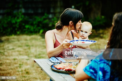 Mother kissing daughter on head during barbecue