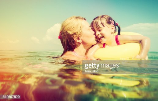 Mother kissing daughter on swimming tube in sea