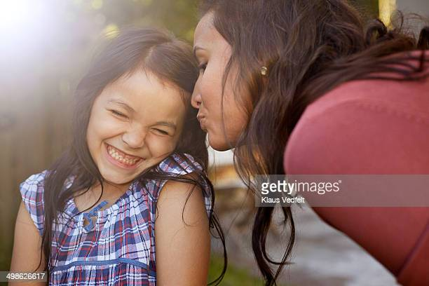Mother kissing daughter on the cheek