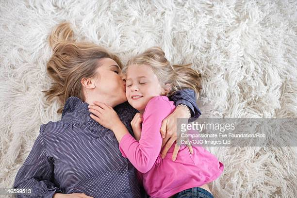 Mother kissing daughter