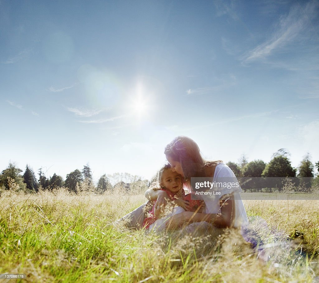 Mother kissing daughter's forehead in rural field : Stock Photo