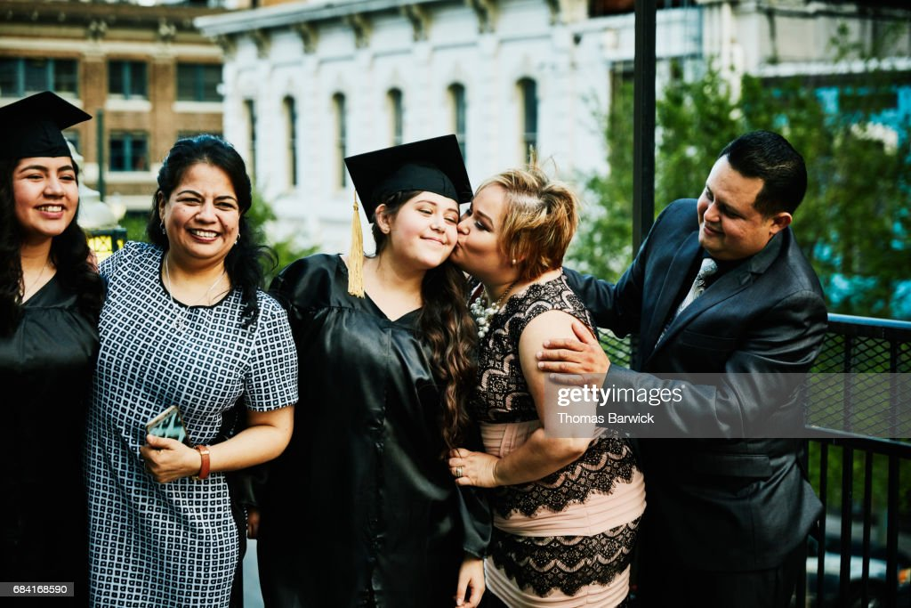 Mother kissing graduating daughter during family celebration on restaurant deck : Stock Photo